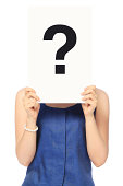 A woman in business attire holding a question mark over her face