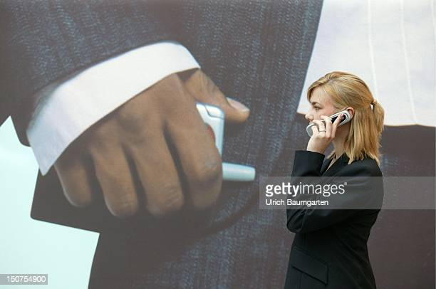 Woman with a Samsung camera mobile phone in front of a video screen with a mobile phone advertisment at the fair CeBIT in Hanover