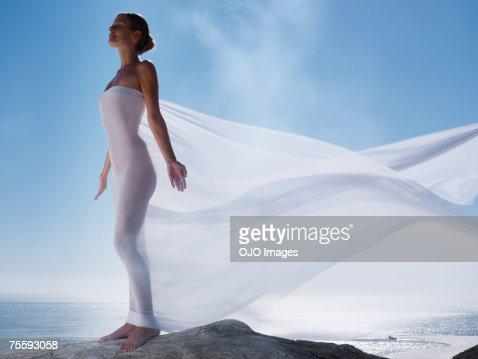 Woman with a sheer sheet with ocean backdrop
