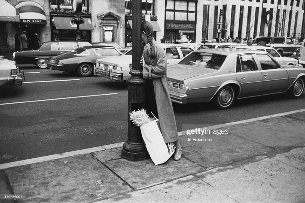 A woman with a shopping bag leans against a lamppost on 5th Avenue and 59th Street New York City 1979