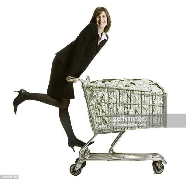 woman with a shopping cart full of money