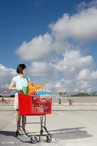 Woman with a Shopping Cart in a Parking Lot