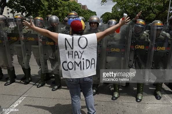 TOPSHOT A woman with a sign reading 'There is no food' protests against new emergency powers decreed this week by President Nicolas Maduro in front...