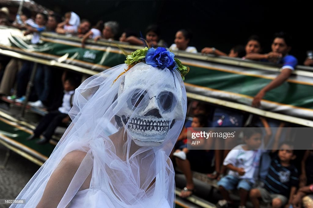 A woman with a skull mask participates in the 'Burial of arrogance and haughtiness' carnival during the IX Poetry Festival in Granada, 45 km from Managua, Nicaragua on February 20, 2013. In this occasion the festival is dedicated to Nicaraguan poet Ernesto Cardenal. AFP PHOTO/Hector RETAMAL