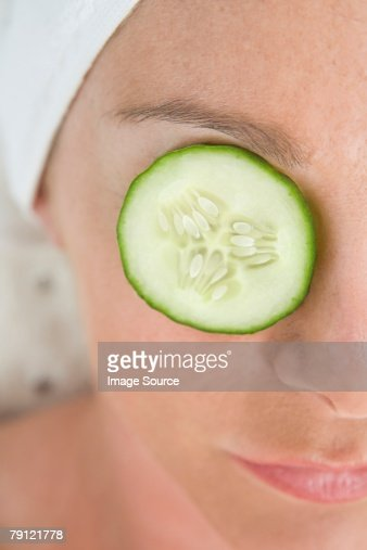 Woman with a slice of cucumber over her eye : Stock Photo