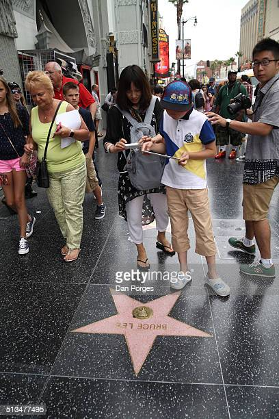 A woman with a smartphone and a boy with a tablet device both photograph the Bruce Lee star on the Hollywood Walk of Fame Los Angeles California July...