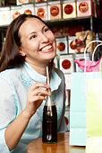 Woman with a soda and gift bags
