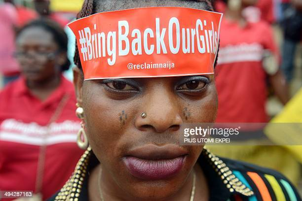 A woman with a sticker on her head bearing the slogan 'Bring back our girls' marches for the release of the more than 200 abducted Chibok school...
