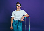 A young smiling woman in summer casual clothes and sunglasses is standing near to a light blue suitcase against a lilac background
