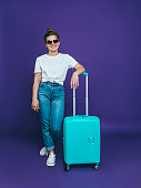 A young smiling woman in summer casual clothes and sunglasses is standing near to a light blue suitcase on a lilac background