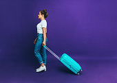 Young traveler woman in summer casual clothes is rolling a suitcase on wheels