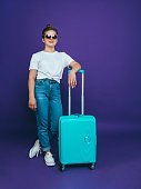 A young woman in a white T-shirt and blue jeans is standing near to a light blue suitcase on a lilac background
