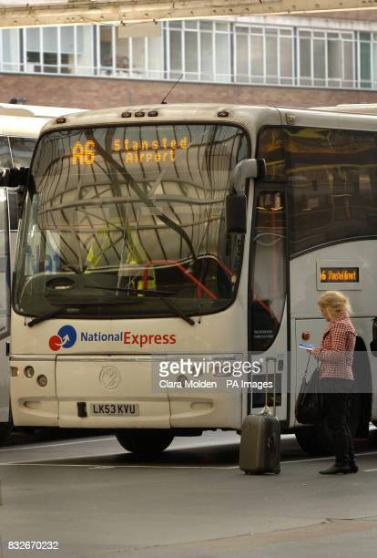 A woman with a suitcase waits to board a National Express coach heading for Stanstead Airport in Victoria coach station London