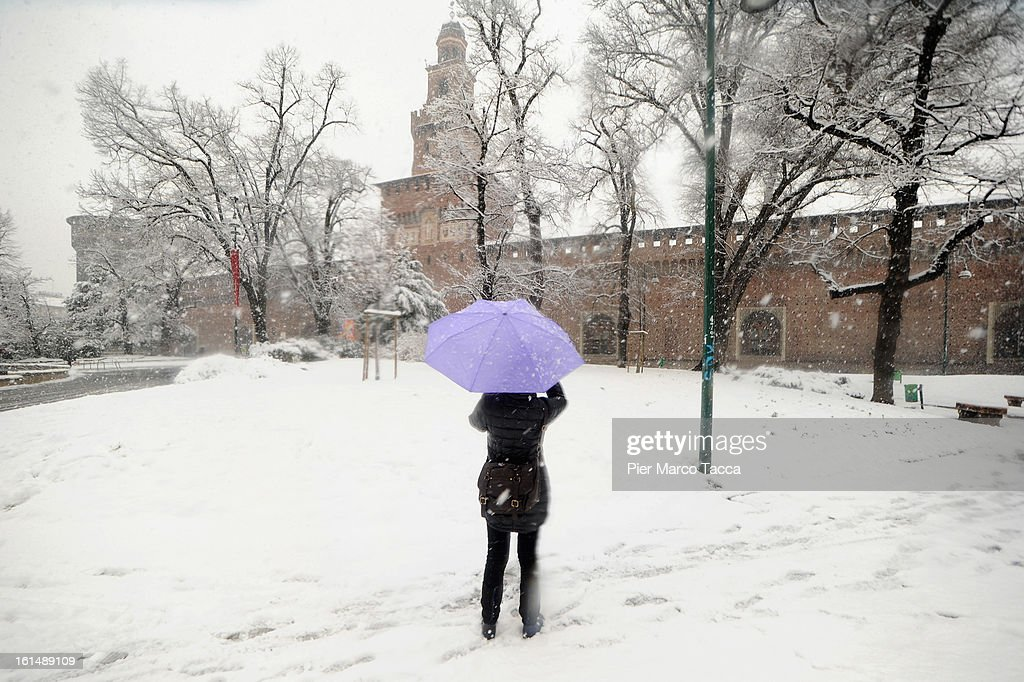 A woman with a umbrella out in the snow in Sforzesco Castle on February 11, 2013 in Milan, Italy on February 11, 2013 in Milan,Italy.Wind, snow and tempetarture under zero over the country has affected regions from North Italy to South Italy, transports has been affected with train cancellations and road closures.