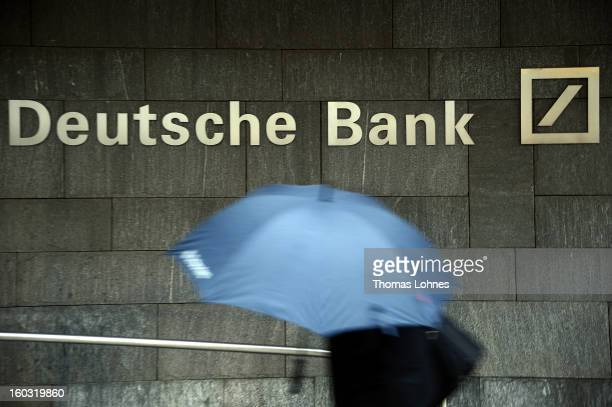 A woman with a umbrella passes a logo of Deutsche Bank on January 29 2013 in Frankfurt am Main Germany The annual results press conference for 2012...