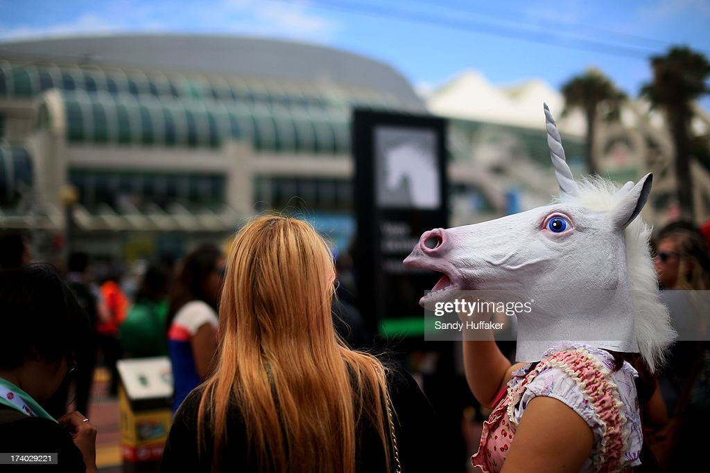 A woman with a unicorn horse head waits in line to cross the street at Comic Con at the San Diego Convention Center on July 19, 2013 in San Diego, California. Comic Con International Convention is the world's largest comic and entertainment event and hosts celebrity movie panels, a trade floor with comic book, science fiction and action film-related booths, as well as artist workshops and movie premieres.
