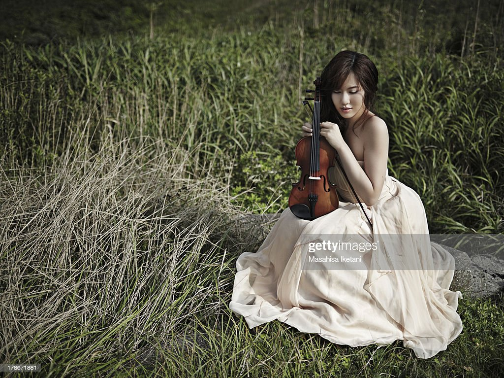 Woman with a violin at grassy plain : Stock Photo