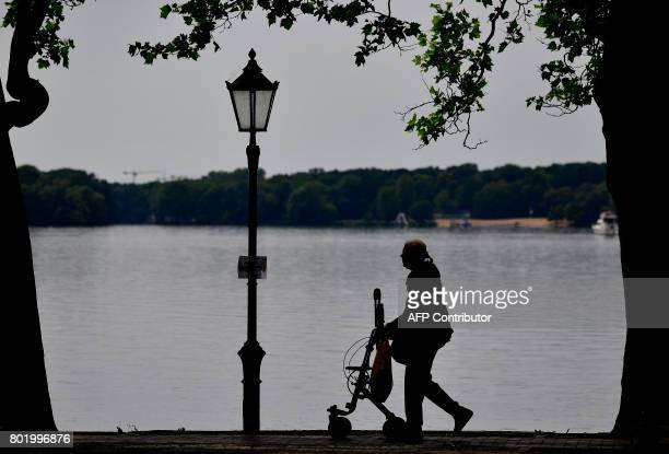 A woman with a walking frame takes a stroll along Tegeler See lake in Berlin on June 27 2017 According to a study of the Bertelsmann foundation...