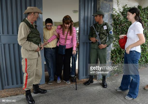 A woman with a walking stick leaves after casting her vote at a polling station during regional elections in Caracas' municipality of Baruta where...