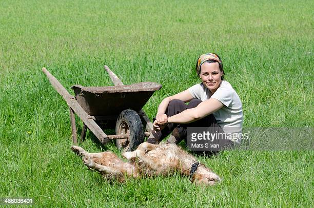 Woman with a wheelbarrow and a dog