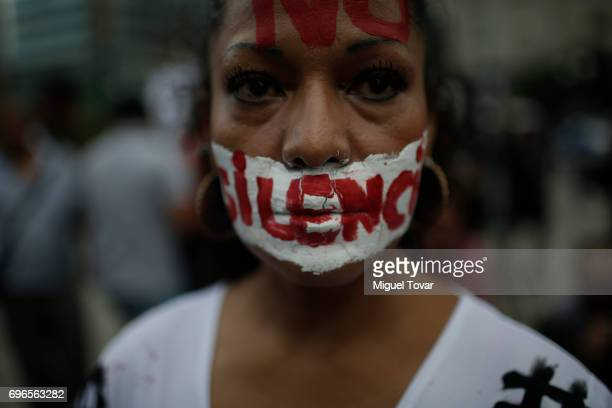 A woman with a writing on her face that reads 'no to silence' looks at the camera during a demonstration to end violence against journalists in...