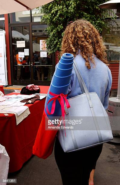 A woman with a yoga mat in her bag attends the Step Up Women's Network's Third Annual 'Step Up For Yoga and Health' charity festival at Bergamont...
