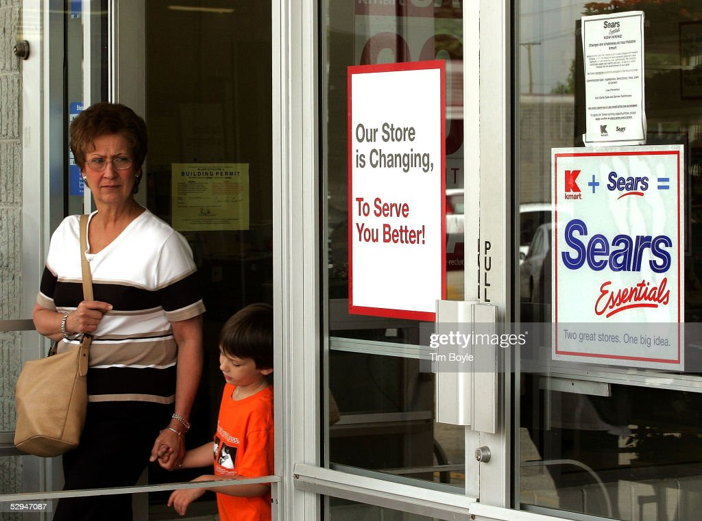 A woman with a young child departs a current Kmart store May 18, 2005 in Palatine, Illinois. This particular Kmart is in transition to become one of Sears' new stores called 'Sears Essentials.' Kmart recently bought Sears, Roebuck and Co. for $12.3 billion.