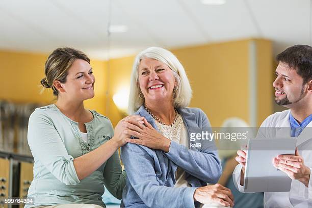 Woman with adult daughter talking to doctor