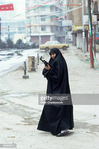 A woman with an AK47 semiautomatic rifle during fighting on the 'Green Line' the no mans land of devastated buildings between East and West Beirut...