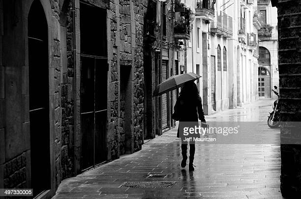 A woman with an umbrella walking in the Gothic quarter of Barcelona.