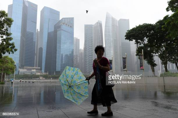 TOPSHOT A woman with an umbrella walks away from the rain in Singapore on March 30 2017 / AFP PHOTO / ROSLAN RAHMAN