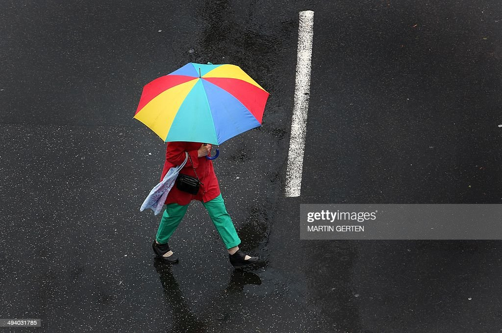 A woman with an umbrella walks on May 27, 2014 in Duesseldorf, Germany. AFP PHOTO / DPA / MARTIN GERTEN / GERMANY OUT