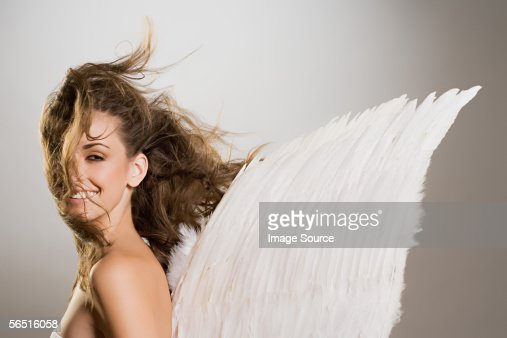 Woman with angel wings and windswept hair : Stock Photo