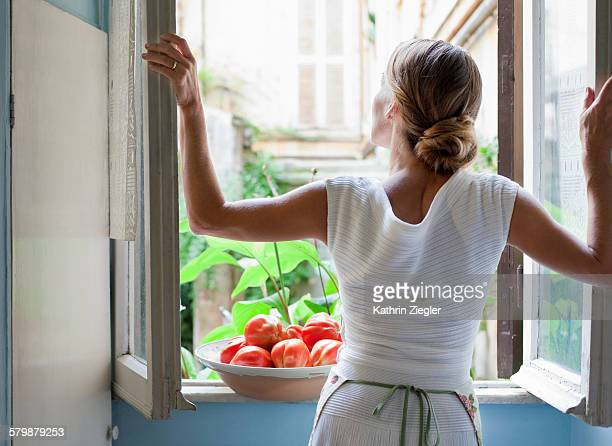 woman with apron at open kitchen window