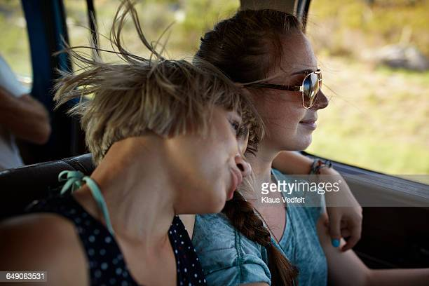 Woman with arm around friend driving car
