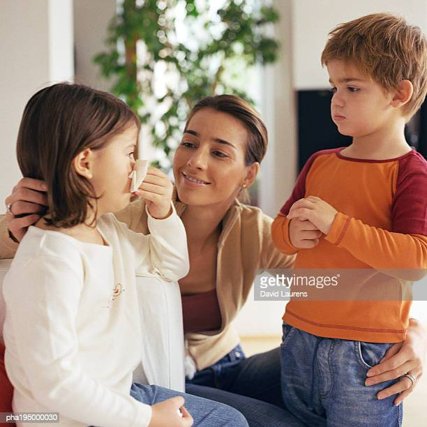 Woman with arms around two children, looking at girl blowing nose.