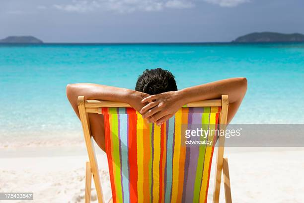 woman with arms behind her head sunbathing at tropical beach