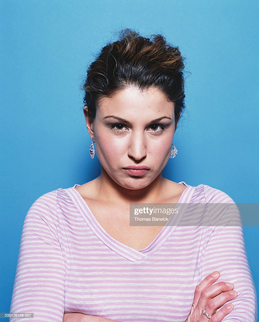 Woman with arms folded across chest and lips puckered, portrait : Stock Photo