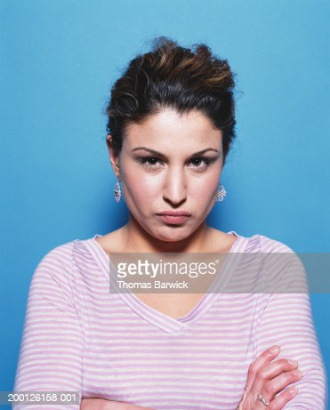 Woman with arms folded across chest and lips puckered, portrait