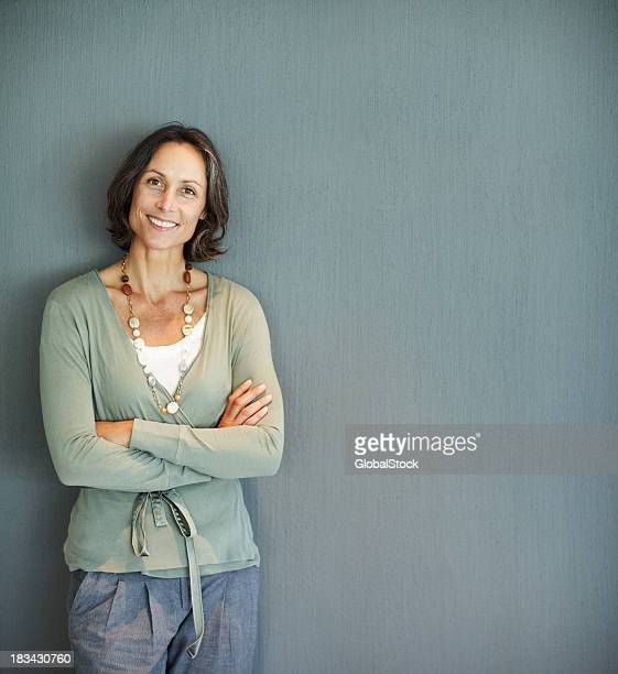 Woman with arms folded against gray background