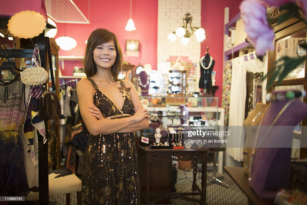 Woman with arms folded in  antique shop : Stock Photo