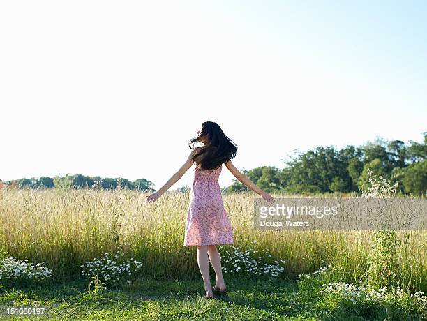 Woman with arms out stretched in countryside.