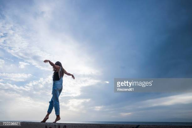 Woman with arms outstretched balancing on wall in front of sky