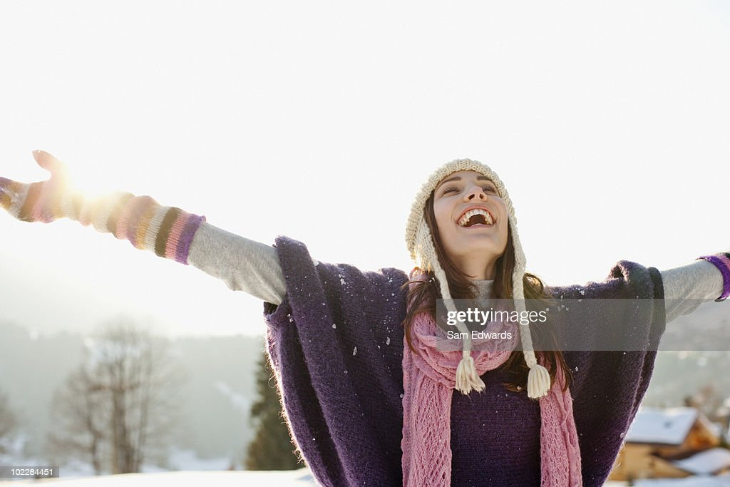 Woman with arms outstretched in snow : Stock Photo