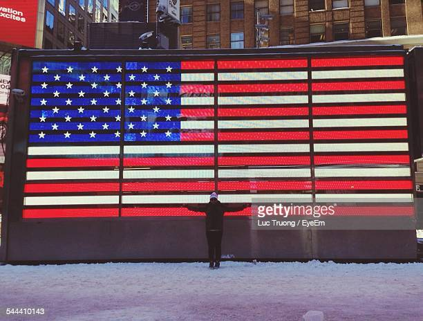 Woman With Arms Outstretched Standing Against American Flag