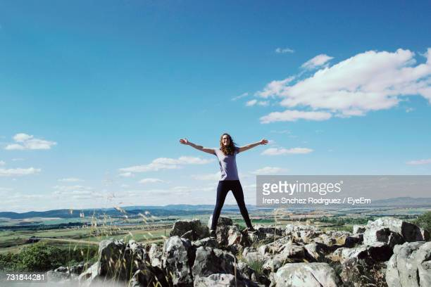 Woman With Arms Outstretched Standing On Rocks Against Sky