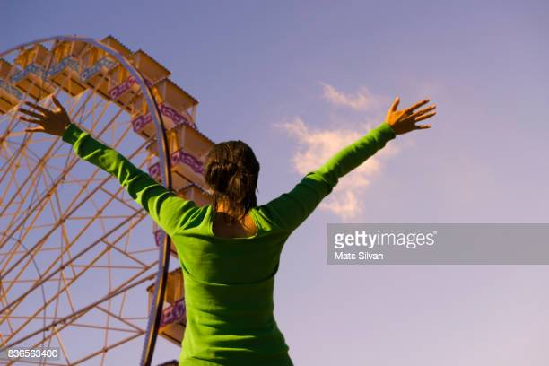 Woman with Arms Outstretched with a Ferris Wheel