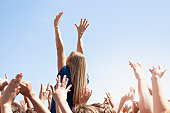 Woman with arms raised above crowd