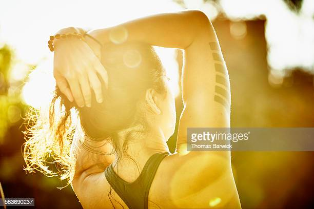 Woman with arms raised overhead looking at sunset