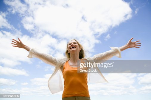 Woman with arms wide open smiling : Stock Photo